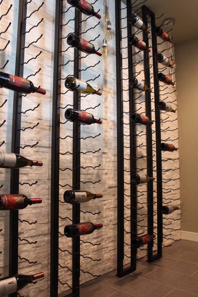 dry stack stone wall behind vertical wine racks
