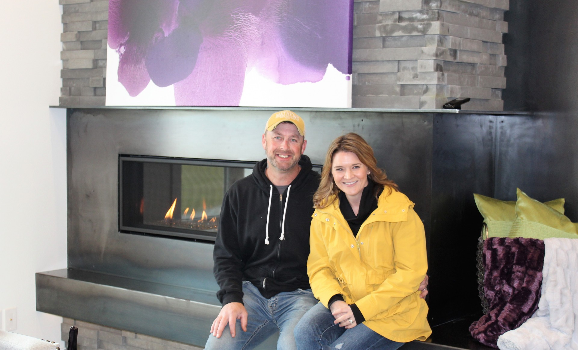 Chris Buttke and his wife Janel in front of dry stacked fireplace