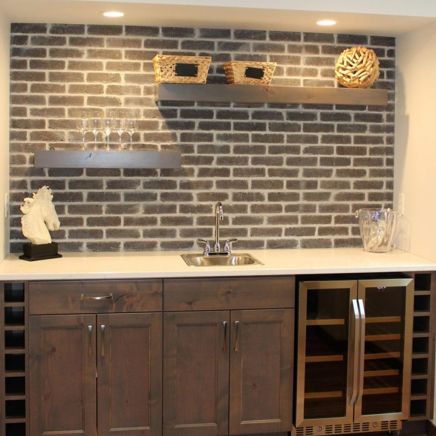 brown brick accent wall with white mortar above wet bar in Fargo home