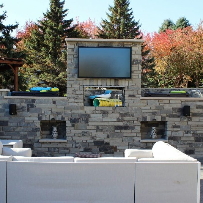 stone tv surround on patio area by OTXteriors in Fargo