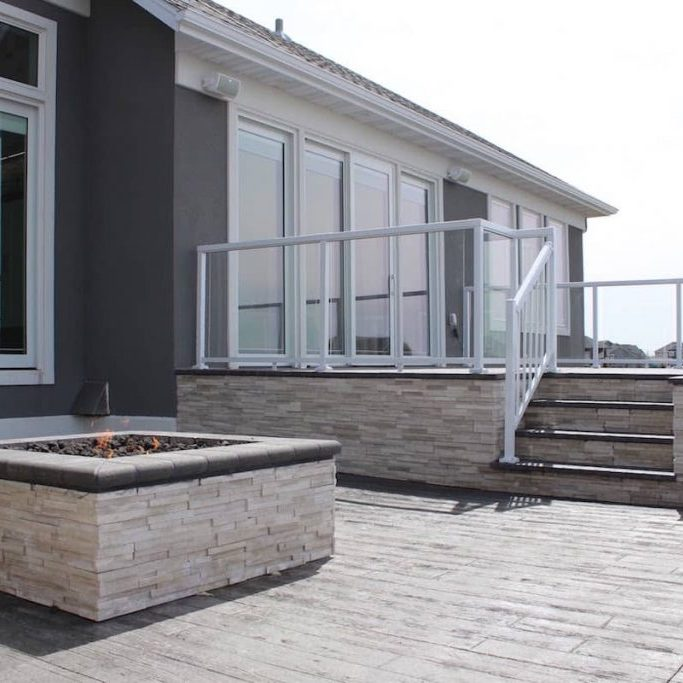 stone patio and walls with stacked stone fireplace by OTXteriors in Fargo